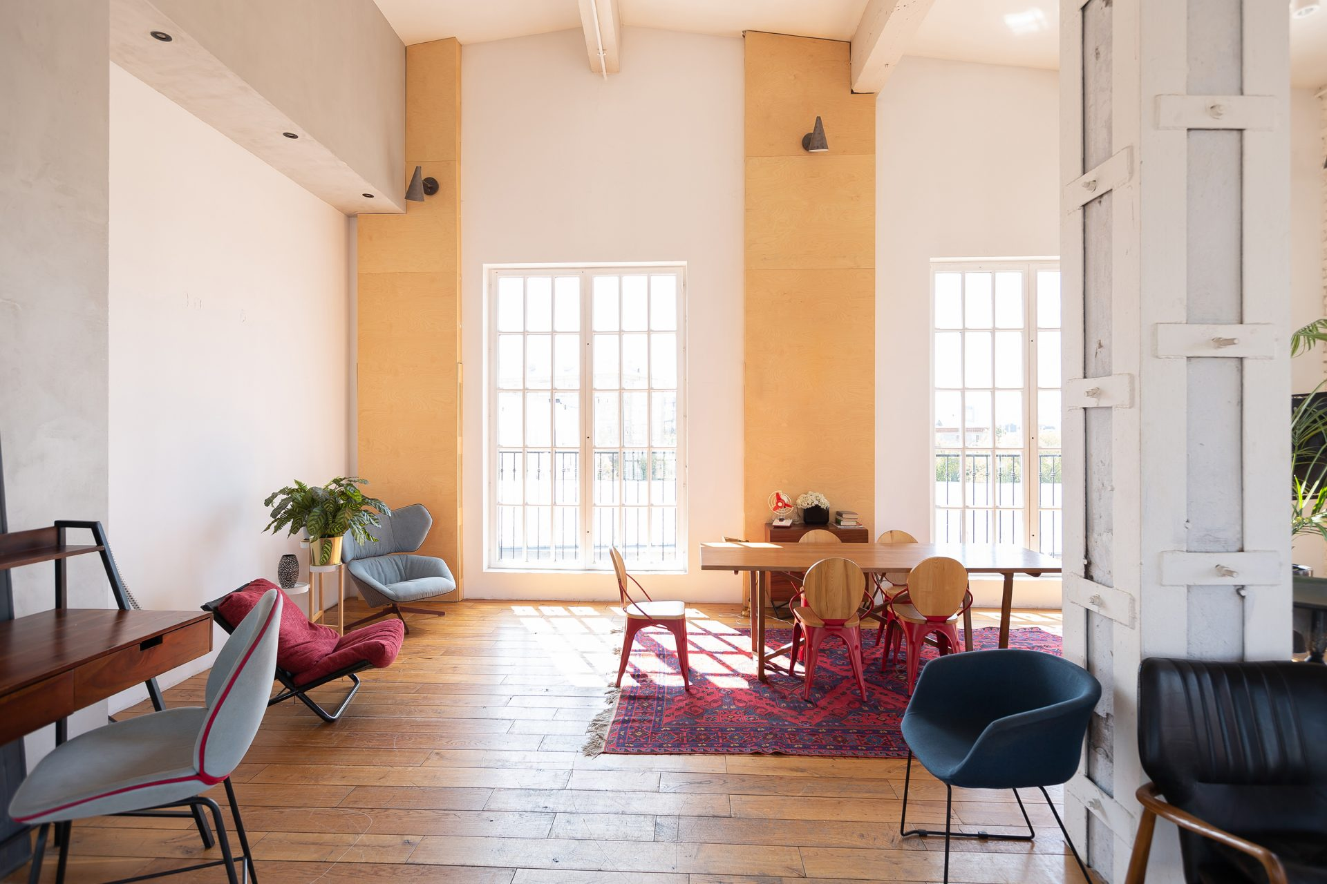 modern-design-of-a-huge-white-bright-room-with-two-red-sofas-and-many-large-windows-full-of-sunshine-high-ceiling-and-wooden-parquet